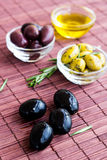 Plates of green olives, black olives and olive oil on bamboo nap Royalty Free Stock Photography