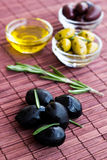 Plates of green olives, black olives and olive oil on bamboo nap Stock Image