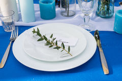 Plates with greenery on the wedding banquet table with blue tablecloth and cutlery, glasses, candles Stock Photo