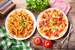 Plates of italian food. Pasta bolognese and ravioli with tomato Royalty Free Stock Photo