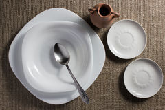 Plates and jug on a table. White porcelain plates and clay pot on a sacking Royalty Free Stock Photos