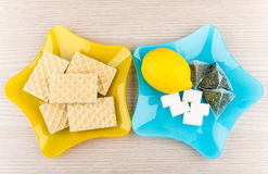 Plates with lemon, sugar, tea bags and wafers on table Royalty Free Stock Images