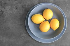 Plates with lemons. On grey background Stock Photography