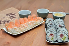 Plates of maki sushi rolls and nigiri sushi with salmon and shrimp japan food on the table with soy sauce Royalty Free Stock Photo