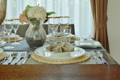 Plates and napkin setting on dining table Stock Photos