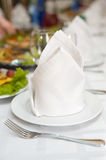 Plates with napkins in perspective. White napkins folded as triangles on plates, in perspective, on laid banquet table, shallow DOF Stock Photography