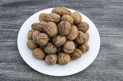Plates of natural walnuts and walnut crumbs A plate of dry walnuts, the most wonderful walnut pictures Stock Images