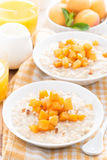 plates of oatmeal with fresh apricots and nuts, orange juice Stock Photos