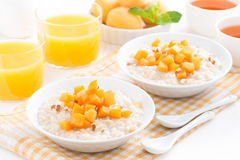 Plates of oatmeal with fresh apricots, orange juice and tea Stock Photo