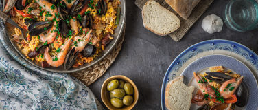 Plates with paella on the dark stone table with different accessories wide screen Royalty Free Stock Photos