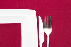 Plates on red cloth with cutlery Royalty Free Stock Photography