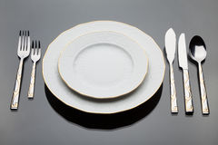 A plates and a set of silverware. On grey glass table stock images