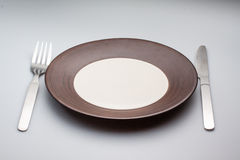 Plates with a silver fork and knife  on gray Royalty Free Stock Images