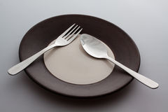 Plates with a silver fork and spoon  Stock Images