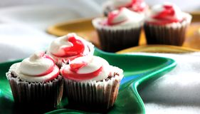 Plates of small cupcakes with red and white icing royalty free stock photography