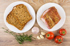 Plates with smoked bacon, bread. Red tomatoes, garlic and rosema Stock Photography