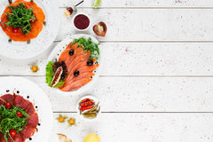 Plates with smoked fish and meat, free space Royalty Free Stock Photos