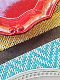 Plates on the table. Brilliant colored plates lying on a summer wooden table Stock Photography