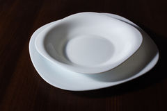 Plates on a table. White plates on a table from a tree Royalty Free Stock Image