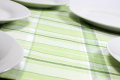 Plates on tablecloth in kitchen Stock Photography