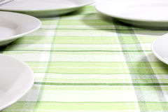 Plates on tablecloth in kitchen Royalty Free Stock Photos