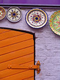 Plates on a wall. Decorative plates on a lilac brick wall in a London street stock photography