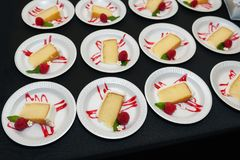 Plates of yellow cake with white frosting and raspberry garnish royalty free stock photography