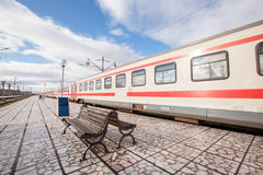 Platform with bench and train at the station Stock Images