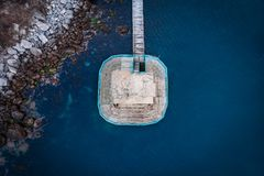 Platform or pier with wooden bridge near sea rocky beach, aerial top view. Summer vacation and travel objects concept.  royalty free stock photography