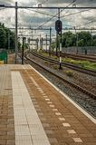 Platform, railroad rails and signaling at train station under blue cloudy sky at Weesp. stock image