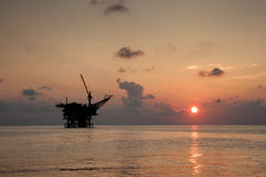 Platform at sea during sunset. Silhouette oil rig platform at sea with sunset stock images