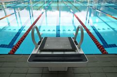 Platform and swimming pool. A solitary starting block against the empty pool Royalty Free Stock Photo