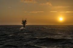 Platform van het Caravel het onbemande gas in ruwe die overzees wordt gesilhouetteerd tegen Royalty-vrije Stock Afbeeldingen