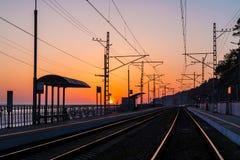 Platforma stacja kolejowa i linia kolejowa przy zmierzchem Zdjęcie Stock