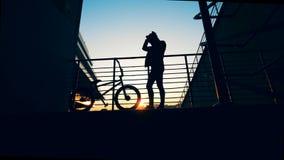 Platforma w zmierzchu z młodym człowiekiem robi jego włosianemu i rowerowej pozyci obok on zbiory wideo