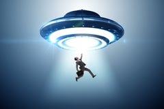 Platillo volante que secuestra al hombre de negocios joven foto de archivo