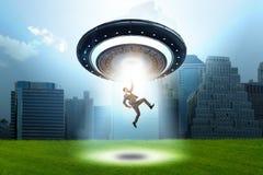 Platillo volante que secuestra al hombre de negocios joven imagen de archivo libre de regalías