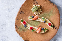 Plating dessert banana. Food plating dessert organic banana with fresh berries, mint, puffed rice and macaroon biscuit served with green tea matcha powder on Royalty Free Stock Images