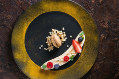 Plating dessert banana. Food plating dessert organic banana with fresh berries, mint, puffed rice and macaroon biscuit served with turmeric powder on black plate Royalty Free Stock Photography