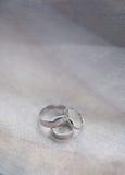 Platinum engagement and wedding ringson on fabric Stock Image