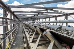 Platinum Mining and Processing of ore, Piles of ore rock being moved and stored. Platinum Mining and Processing of ore, Platinum rock being moved on a conveyor Royalty Free Stock Image