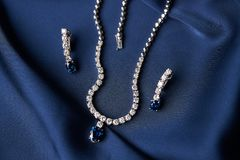 Platinum necklace and earrings with a diamond and blue precious. Women`s platinum necklace and earrings with a diamond and blue precious sapphire stone on a silk stock photography
