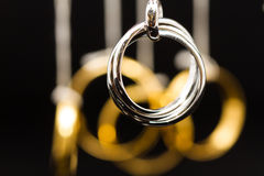 Platinum rings pendant. Hanging platinum rings pendant with gold rings on background Stock Photos