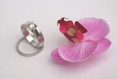 Platinum wedding rings. Stunning diamond engagement and wedding rings in platinum with a pretty pink briday orchid for decoration Stock Photo
