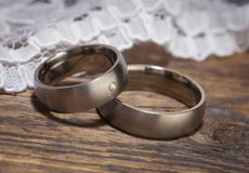 Platinum wedding rings on wooden table. With lace in background Stock Image