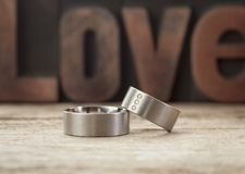 Platinum wedding rings in front of word Love. Platinum wedding rings on wooden table, word Love in background Royalty Free Stock Photo