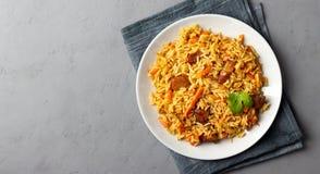Plato asiático - pilaf del arroz, de verduras y de la carne en una placa en fondo gris fotos de archivo