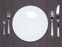 Plato, bifurcación, cuchara y cuchillo blancos en blanco Fotografía de archivo