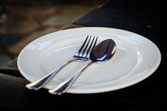 Plato blanco con la cuchara y la bifurcación Foto de archivo libre de regalías