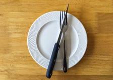 Plato blanco con la gente y el cuchillo en la tabla de madera Imagen de archivo